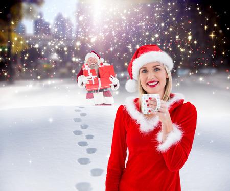 pere noel sexy: blonds Festive tenant une tasse contre le p�re livrer des cadeaux dans la ville Banque d'images