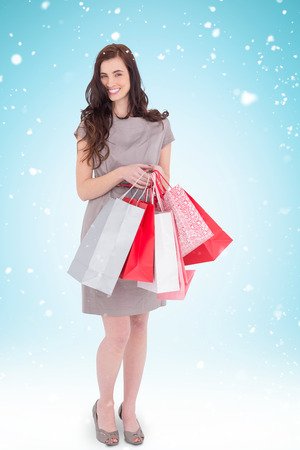 gift spending: Elegant and smiling brunette with shopping bags against blue background with vignette