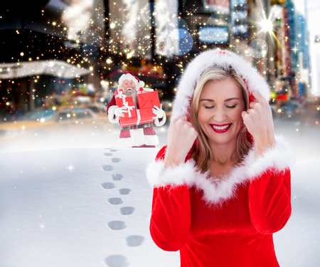 pere noel sexy: Festive blonde with hood up against santa delivering gifts in city