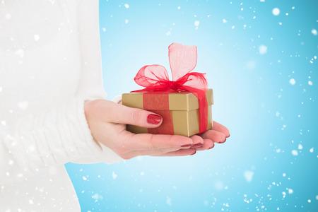 gild: Pretty woman holding gild gift  against blue vignette