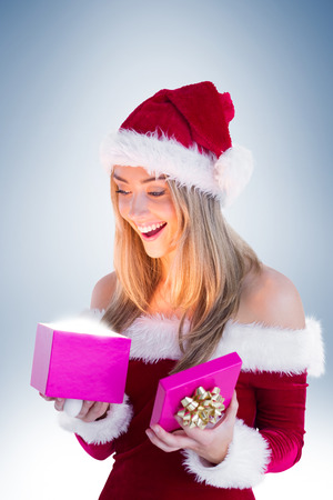 Festive blonde opening a gift on vignette background Stock Photo