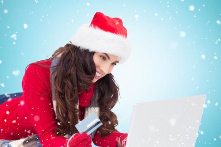 holiday spending: Happy brunette shopping online with laptop against blue vignette