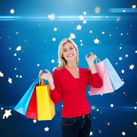 lucero: Happy blonde holding shopping bags against bright star pattern on blue