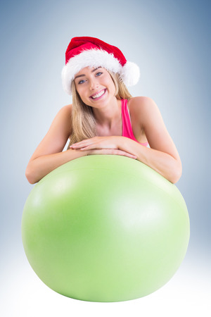 exercise ball: Festive fit blonde posing with exercise ball on vignette background Stock Photo