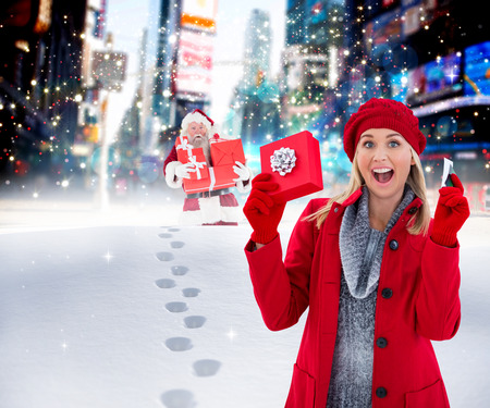 adult footprint: Festive blonde holding gift and credit card against santa delivering gifts in city