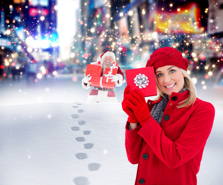 adult footprint: Festive blonde holding red gift  against santa delivering gifts in city