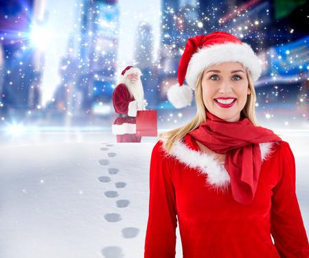 pere noel sexy: Festive blonds souriant � la cam�ra contre Santa livraison des cadeaux dans la ville