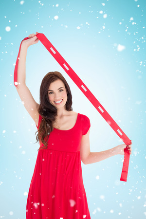 evening wear: Stylish brunette in red dress holding scarf against blue background with vignette