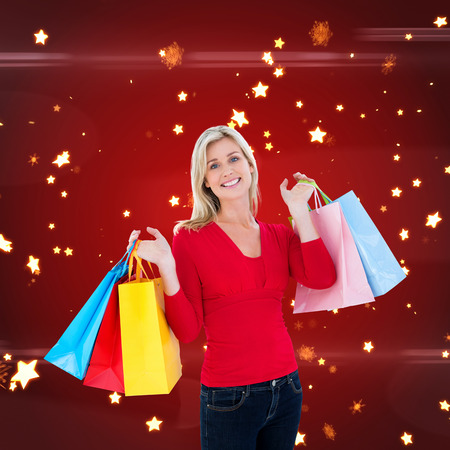 lucero: Happy blonde holding shopping bags against bright star pattern on red
