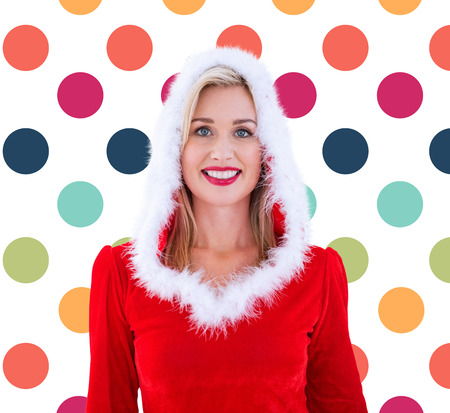 polka dot pattern: Festive blonde smiling at camera against colorful polka dot pattern