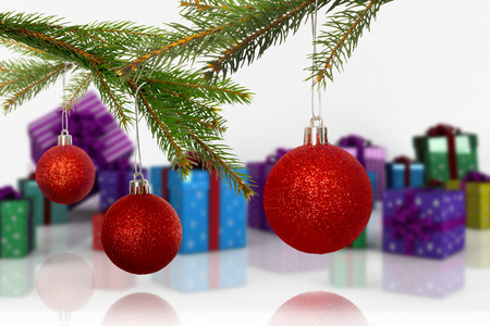 many christmas baubles: Baubles on tree against many colourful christmas gift boxes