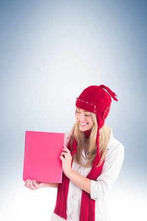 red cardigan: Pretty blonde showing red poster on vignette background Stock Photo