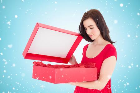 opening gift: Stylish brunette in red dress opening gift against blue vignette