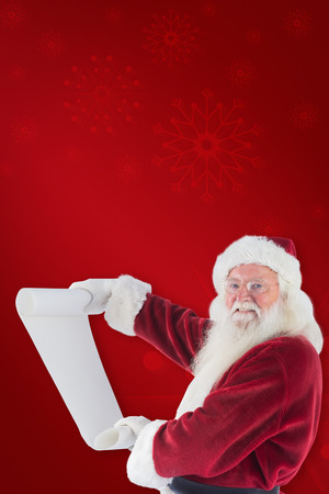 pere noel: Father Christmas holds a list against red background