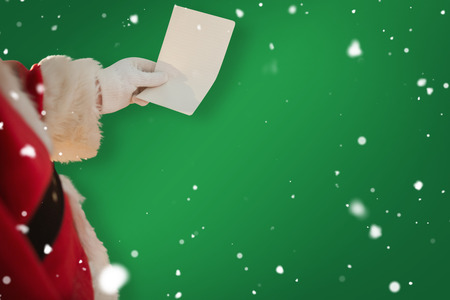 pere noel: P�re No�l tenant un papier contre verte Banque d'images