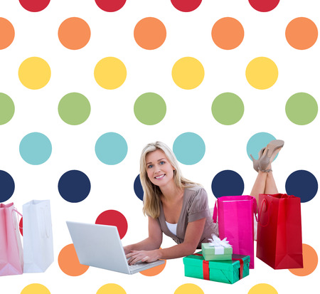 polka dot pattern: Happy blonde shopping online with laptop against colorful polka dot pattern