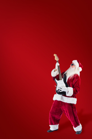 lean back: Santa playing electric guitar against red background