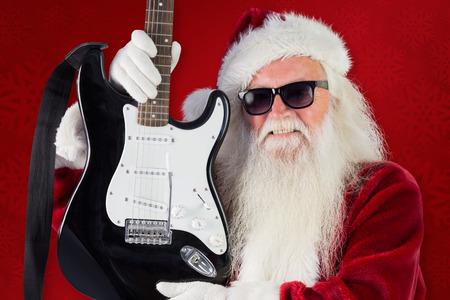 pere noel: Le P�re No�l montre une guitare sur fond rouge Banque d'images