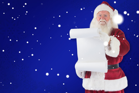 pere noel: Father Christmas holds a list against blue Banque d'images