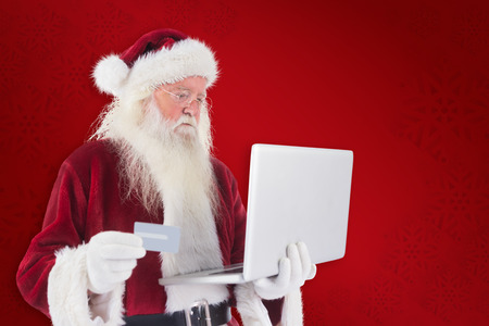 pays: Santa pays with credit card on a laptop against red background