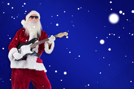 lean back: Santa Claus plays guitar with sunglasses against blue snowflake background Stock Photo