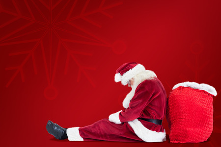 leaned: Santa sits leaned on his bag against red background