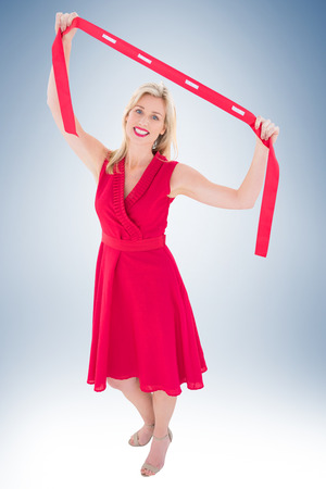 evening wear: Stylish blonde in red dress holding scarf on vignette background