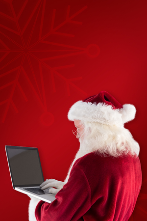 clear away: Santa Claus uses a laptop against red background
