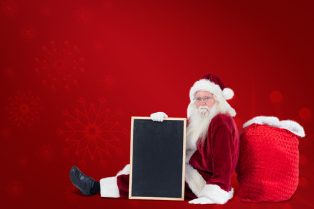 copy sapce: Santa sits leaned on his bag with a board against red background Stock Photo