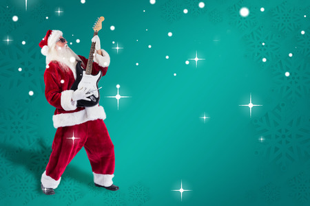 lean back: Santa playing electric guitar against green snowflake background Stock Photo