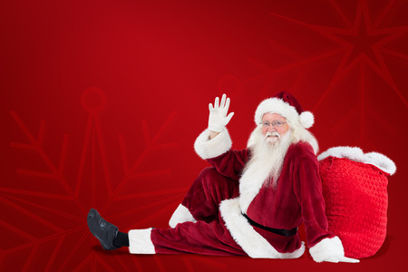 leaned: Santa sits leaned on his bag and waves against red background Stock Photo