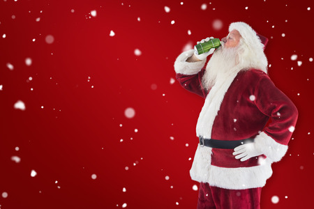 Father Christmas drinks beer with closed eyes against red background Stock Photo
