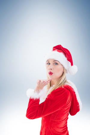 pere noel sexy: Festive blonde blowing a kiss on vignette background Banque d'images