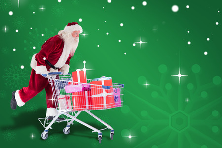 pushes: Santa pushes a shopping cart against green snowflake background