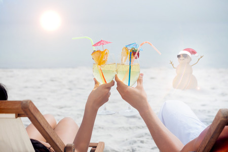 clinking: Couple clinking glasses of cocktail on beach against festive sandman Stock Photo