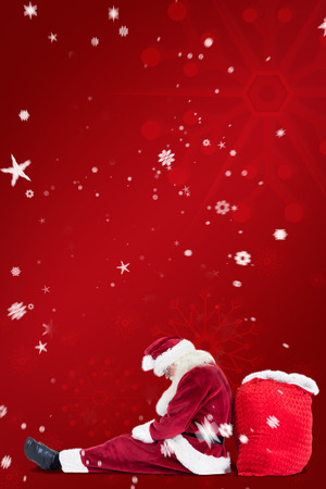 leaned: Santa sits leaned on his bag against red snowflake background Stock Photo
