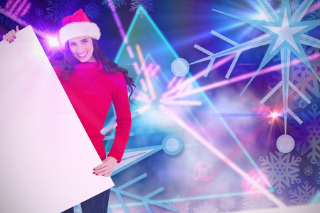 laser lights: Smiling brunette in santa hat showing white poster against digitally generated laser lights background