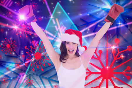 laser lights: Festive brunette in boxing gloves cheering against digitally generated laser lights background