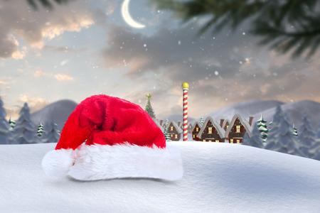 north pole: Santa hat on snow against cute christmas village at north pole