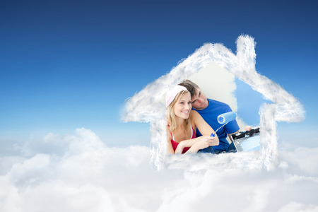 Affectionate couple painting a room against blue sky over clouds