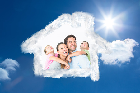 family looking up: Happy young family looking up together against bright blue sky with clouds