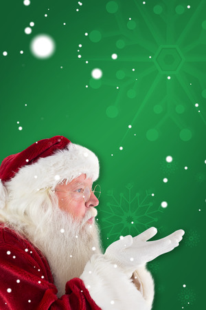 blows: Santa Claus blows something away against green snowflake background