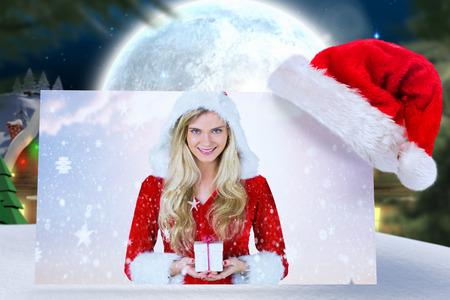 pere noel sexy: jolie fille � santa outfit tenant cadeau contre ville pittoresque avec lune brillante Banque d'images