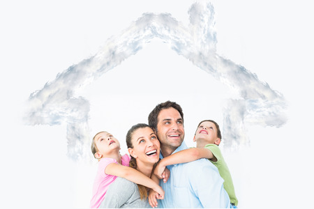 family looking up: Happy young family looking up together against house outline in clouds