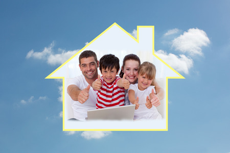 cloudy home: Family at home using a laptop with thumbs up against cloudy sky Stock Photo