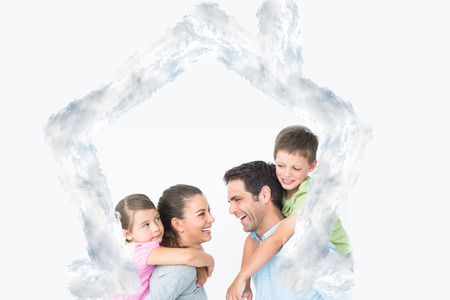 house outline: Cheerful young family posing against house outline in clouds Stock Photo