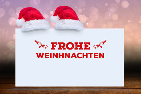 frohe: frohe weinhnachten against shimmering light design over boards Stock Photo