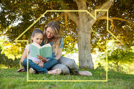 Mother and daughter reading a book at park against house outline Stock Photo