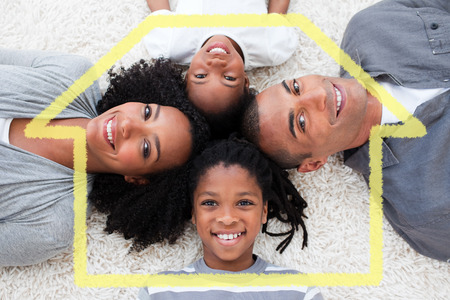 house outline: Smiling young family lying on floor against house outline