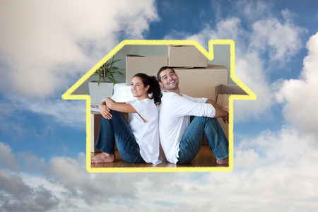 mortage: Bright couple with unpacking boxes moving to a new house against blue sky with white clouds
